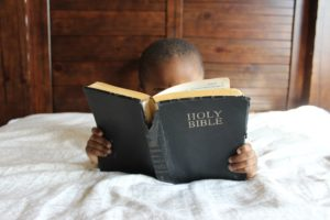 Child Reading Bible For Baptism